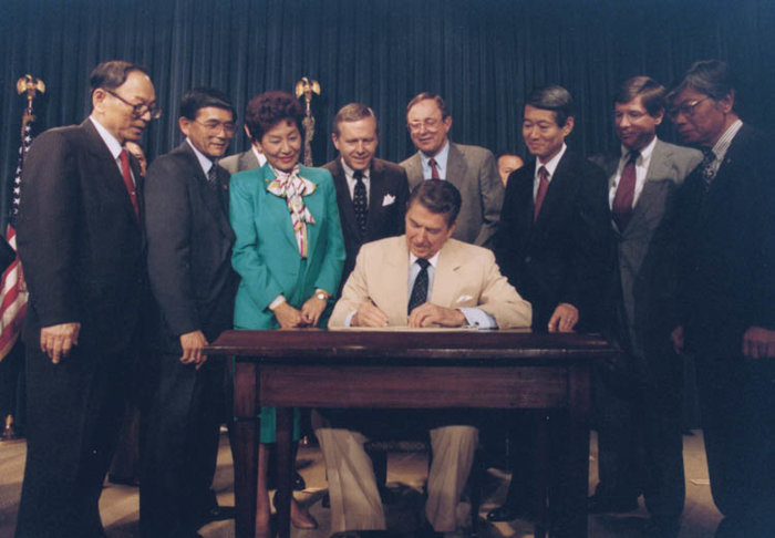 Ronald_Reagan_signing_Japanese_reparations_bill.jpg