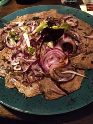 Slices of beef in vinaigrette with red onions and styrian pumpkin seed oil.jpg